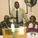 Elder Charles Cooper, standing, flanked by his father, Sylvester Cooper, and mother, Bertha Cooper, speaks at Bertha's 80th birthday celebration in 2005.