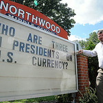Michael Basinski, principal at Northwood Middle School, stands next to the sign at the school's entrance on Gulf Road. He poses questions for drivers to ponder while waiting at the traffic …