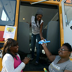 Makeisha Price, 16, and LaVonda Sims, 16, hand school supplies to Bre-Aja Tucker, 17, all of Lorain, to stuff the school bus outside of Credit Recovery Academy on Aug. 14. KRISTIN BAUER | C …