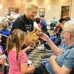 Jesse Cantrell reaches out to pet Clyde, who is held by Friendship APL volunteer Donna Biggar, of Avon Lake, on Aug. 15 at Wesleyan Village's dog days of summer dog show. KRISTIN BAUER | CHR …