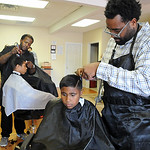 Damien Hennessse, 10, of Lorain, front, has his hair cut by owner Mario Kirk at Red Carpet Haircutting Salon, 914 Broadway in Lorain, on Aug. 18. In rear, is Dylan Bekely, 12, of Lorain, ge …