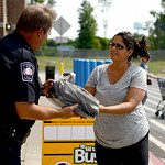 Johana Bierek, of Avon, and an Amherst teacher, hands a bag full of donated school supplies to school resource officer Pat Sullivan during the Fill the Bus event at Walmart in Avon on Aug. 8 …