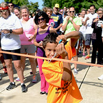 Runners and walkers line up behind Murray Ridge primary student Patrick Boey, 11, of Grafton, as he cuts the ribbon to begin the Strides for Struggles 5K on Aug. 16. KRISTIN BAUER | CHRONICL …