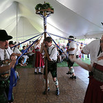 Brent Miller of Lorain holds up the maypole for his fellow STV Bavaria dancing group at the German Heritage Festival at the Sandstone Historical Center in Amherst on Aug. 9. BRUCE BISHOP/CHR …