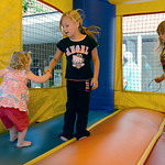 Ryleigh Fracchione, 7, and sister Adrianna, 5, both of Lorain, show Kendra Mae Corl, 2, of Elyria, the ropes of bouncing on Aug. 16 at the Elyria YWCA. KRISTIN BAUER | CHRONICLE