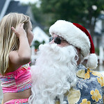 Lana Geib, 6, of Santa Barbra, Calif., greets Santa at Vermilion's annual Christmas in July festivities on July 25 while visiting her grandpa in Vermilion. KRISTIN BAUER | CHRONICLE