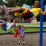 Alayzia Jackson, 11, front, Tatum McNeal, 8, and Brianna West, 10, play on the swings at the Boys and Girls Club of Elyria on July 16.  KRISTIN BAUER | CHRONICLE