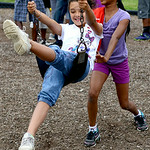 Tatum McNeal, 8, swings with the help of her friend Brianna West, 10, at the Boys and Girls Club of Elyria on July 16.   KRISTIN BAUER | CHRONICLE