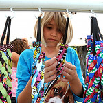Samantha Retuerto, 10, of Avon Lake, browses through the headbands at Sheila Bee headbands of Westlake at the ninth annual Summer Market at Veteran's Memorial Park in Avon Lake on July 25.   …