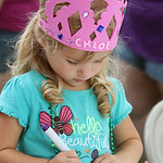 Chloe Rivera-Lough, 2, carefully colors a butterfly sun catcher during the annual Voice for Children Family Fun Day in Ely Square on July 20. ANNA NORRIS/CHRONICLE