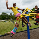 Alayzia Jackson, 11, Deondre Hage, 8, and Toviel Jackson, 10, play on top of a playground structure as Kailyn Burnside, 11, rotates the top at the Boys and Girls Club of Elyria on July 16.   …