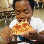 28july14 bishop— Sincer Young, 12 of Elyria  (cq) has pizza that was brought to the Salvation Army in Elyria by the Little Ceasers Love Kitchen. The tractor trailer kitchen has served more …