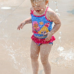 Ava Coker, 2, of Grafton, puts her foot over one of the North Park Splash Pad jets on July 22. KRISTIN BAUER | CHRONICLE
