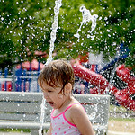Charley Kosovich, 2, of Grafton, splashes in the water at the Splash Pad in Grafton on July 22. KRISTIN BAUER | CHRONICLE