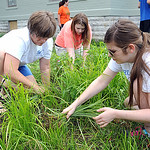 Mary South, front, of Columbia, Tenn., with Sara Embrey, of Senatobia, Tenn, and Molly Pevahouse, rear, of Columbia, Tenn., clear the flower garden for planting at We Carer/We Share Ministri …