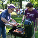 Claudia Kell, of Hudson, Wis., and Gabriel Campbell, of Belle Fountain, Ohio, cook hotdogs for a community picnic on July 24.  KRISTIN BAUER | CHRONICLE