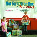 Shanya Adkins, 9, and Landry Adkins, 4, drop off toys.