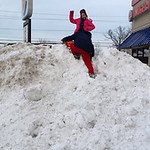 Tara Revercomb's kids couldn't resist climbing the snow mountain in front of the Burger King on West River Road.