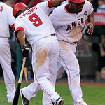 Los Angeles Angels' Howie Kendrick, right, celebrates with Chone Figgins after Kendrick scored on a sacrifice fly by Maicer Izturis during the seventh inning of Game 3 of the American League …