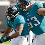 Jacksonville Jaguars wide receiver Mike Thomas, left, flexes for fans as he gets a pat on the back by center Brad Meester (63) after a scoring a touchdown during the first half of an NFL foo …