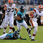 Cleveland Browns quarterback Colt McCoy (12) out runs the tackle of Jacksonville Jaguars defensive end Larry Hart (59) and Jacksonville Jaguars linebacker Daryl Smith (52) for yardage during …