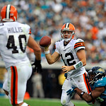 Cleveland Browns quarterback Colt McCoy (12), in the grasp of Jacksonville Jaguars defensive end Larry Hart, right, throws a pass to Browns' Peyton Hillis (40) for an 11-yard touchdown duri …