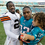 Cleveland Browns cornerback Eric Wright, left, greets Jacksonville Jaguars running back Maurice Jones-Drew, center and his son Maurice Jones-Drew Jr. after an NFL football game in Jacksonvil …