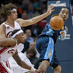 Denver Nuggets guard J.R. Smith, right, passes the ball past Cleveland Cavaliers guard Daniel Gibson, lower left, and Anderson Varejao in overtime in an NBA basketball game Thursday, Feb. 18 …