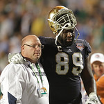 Notre Dame's Kapron Lewis-Moore is helped off the field during the first half of the BCS National Championship college football game against Alabama Monday, Jan. 7, 2013, in Miami. (AP Photo …