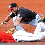 Crushers #6 Kevin Berard dives safely back to third as the Freedom's #3 Edwin Padua tags him.