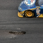 Kurt Busch drives past the broken asphalt in the track, between the first and second red-flag periods, during the NASCAR Daytona 500 auto race at Daytona International Speedway in Daytona Be …