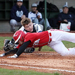 Elyria's Mike Parron dives for home plate as Lorain catcher Nate Drabiak tags him out in the first inning in the Rube Foster Classic last night at The Pipe Yard in Lorain. (CT photo by Anna  …