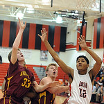 Avon Lake's Seth Muck, left, puts up a shot as Elyria's Anthony Duckett and Avon Lake's Brad Hamilton ready for a rebound. STEVE MANHEIM/CHRONICLE