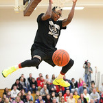 Ronnie Smith hangs from the rim after his slam dunk in the dunk competition at Oberlin College. photo by Ray Riedel