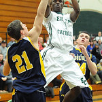Elyria Catholic's DJ Graham shoots between North Ridgeville's Tyler Rowe and Jordan Montgomery. STEVE MANHEIM/CHRONICLE