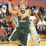 Elyria Catholic's Conner RIddell drives to the basket past Oberlin's Charles Lewis. STEVE MANHEIM/CHRONICLE