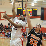 Elyria's Trenell Oliver puts up a shot over Normandy's Jaret Colovas. STEVE MANHEIM/CHRONICLE