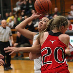 EC's Josie Carandang shoots with one hand as her other arm is held down by Ari Tomasula of Lutheran West. photo by Ray Riedel