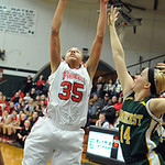 Elyria Alexis Middlebrooks puts up shot over Amherst Mallory Sliman in first half of Div I district Feb. 27. Steve Manheim