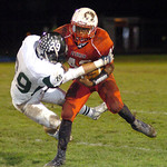 Elyria's Jumarr Lewis runs for yardage with Medina's Dayln Herrmann hanging on. LINDA MURPHY/CHRONICLE