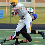 Stripes' Tommy Glenn of Avon is tackled by Daniel Loub of Columbia. STEVE MANHEIM/CHRONICLE
