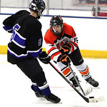 ANNA NORRIS/CHRONICLE<br/>North Olmsted&#039;s Nate Schmitt pushes the puck up the ice against Midview&#039;s Jacob Scheetz Sunday afternoon at the North Olmsted Recreation Center.