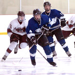 Midview's #4 Bradley Urig moves the puck down the ice in front of Rocky River's #16 Michael Ittu. Midview's #11 Kyle Kudela backs him up.