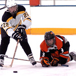 Amherst's #22 Connor Morris works the puck past North Olmsted's #9 Alexander Arendec.