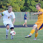 Avon's Will Sharer, right, kicks away from North Ridgeville's Andy Wiles. STEVE MANHEIM/CHRONICLE