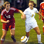 Elyria's No. 12 Michelle Mariner fights North Ridgeville's No. 7 Elizabeth Browning for the ball.