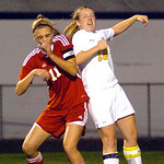 North Ridgeville's No. 18 Marissa Austin heads the ball away from Elyria's No. 11 Monica Backs.