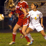 Elyria's No. 11 Monica Backs heads the ball away from North Ridgeville's No. 4 Kayla Zingale.