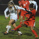 Elyria Catholic's Anna Griffin, left, tries to control the ball as Lutheran West's Taya Hampton closes in Monday night in a rainy Division III district semifinal. STEVE MANHEIM/CHRONICLE