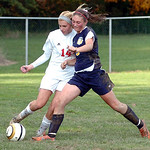 Elyria's #14 Erin Mariner fights North Ridgeville's #5 Anna Chalkley for the ball.